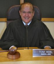 Judge Tom Hebl sitting behind judge's bench with robes on