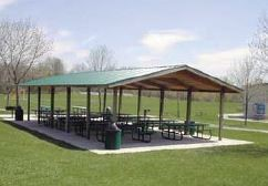 Park shelter with picnic tables in an open grassy area
