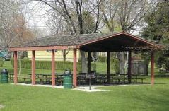 Picnic shelter in a park area with picnic tables and a bbq grill